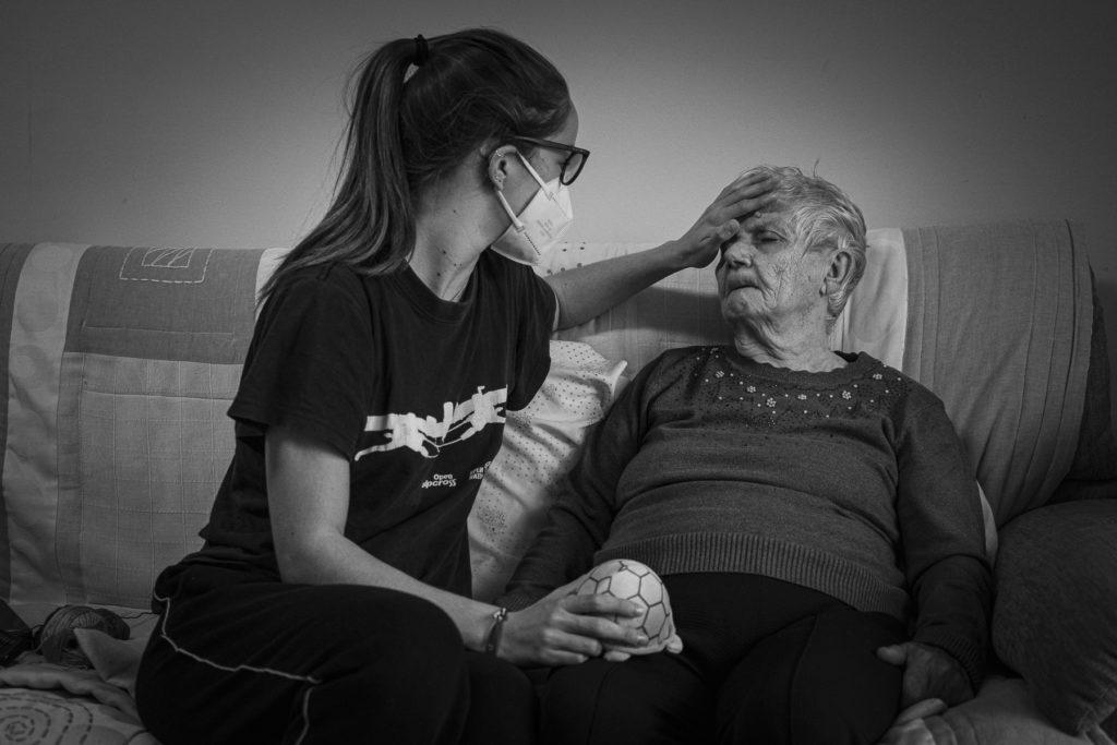 La Laia, néta de la Fina, li comprova la temperatura corporal amb la mà.