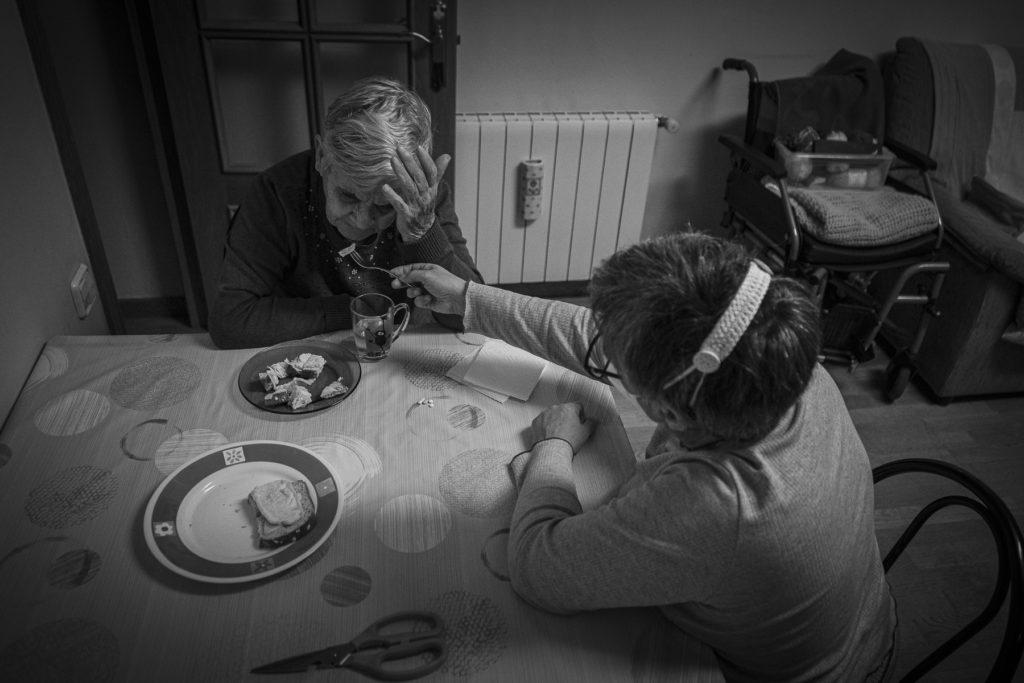 La Núria dóna el sopar a la seva mare, mentre ella gesticula en contra amb la mà.